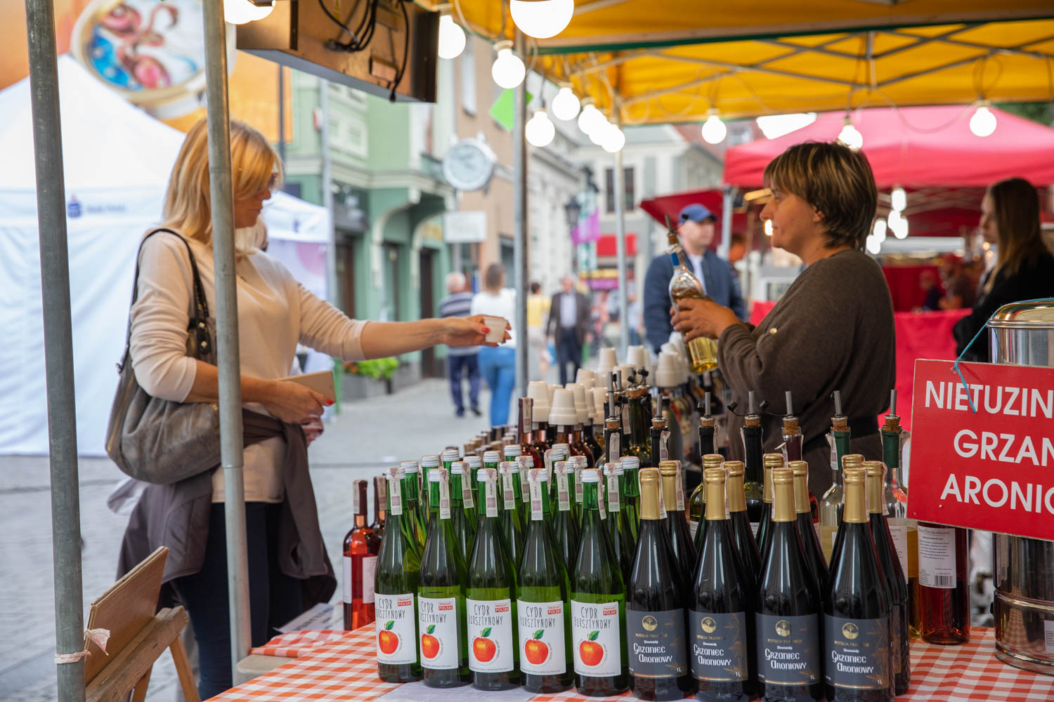 Woman tasting wine and cider at a small booth in the city center
