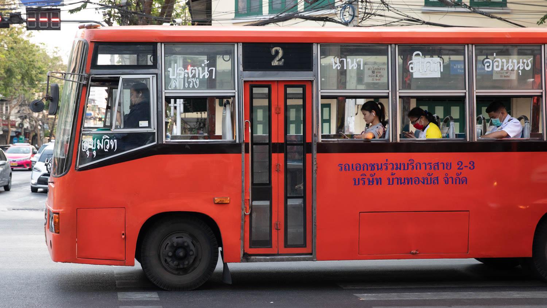 Red Bus in Thailand. People looking down in mobile phones